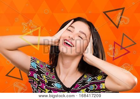 Beautiful smiling girl, with straight dark hair, wearing on colorful shirt, posing on the orange geometric background with colorful triangles and sea set anchor, starfish, dive mask icons, in studio, waist up