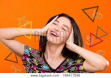 Beautiful smiling girl, with straight dark hair, wearing on colorful shirt, posing on the orange background with colorful triangles and sea set anchor, starfish, dive mask icons, in studio, waist up