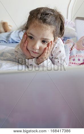 Little girl lying in bed and playing with a laptop in his bedroom. She looks inattentive