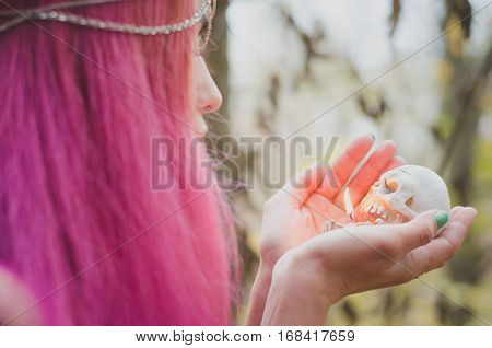 Young pink-haired witch with a skull candle in her hands soft focus faded colors