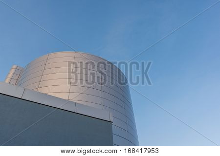 Frederikssund,  Denmark, January 6, 2017: Oil cistern at a termal power plant. A greyish building and a silver cistern against blue sky