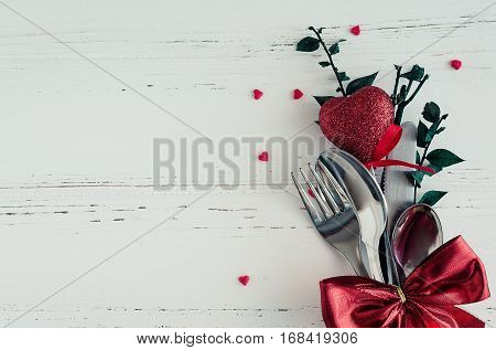 Valentine's Day tabble setting with cutlery on white shabby chic background. Valentine's Day place setting cutlery on white wooden background. Romantic love Valentines concept. Copy space. Top view.