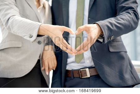 Closeup of loving couple standing side by side at the terrace. Happy Young businessman making a heart shape with his girlfriend. Valentines Day loving concept. Copy space.