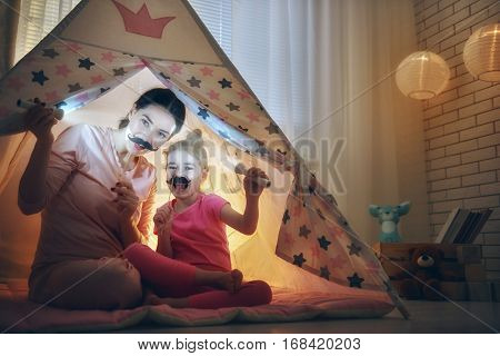 Happy loving family. Young mother and her daughter girl play in children room at the bedtime. Funny mom and lovely child are having fun with flashlights indoors.