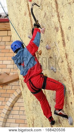 Tyumen, Russia - March 31, 2012: Rock climbing wall of Alkor club. Ice climbing competition. Man climbs upward