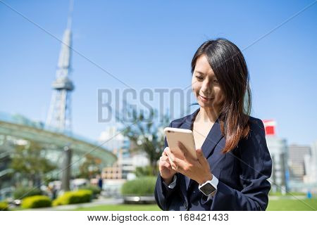 Asian businesswoman uaing cellphone in Nagoya city