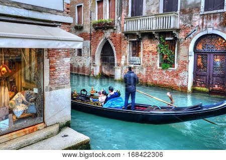 Gondolier transporting tourists on gondola, on the famous Grand Canal of Venice - Italy