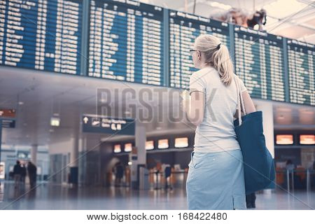 Young blonde woman with tickets in her hand and shoulder bag checking flight timetable in international airport - travel concept