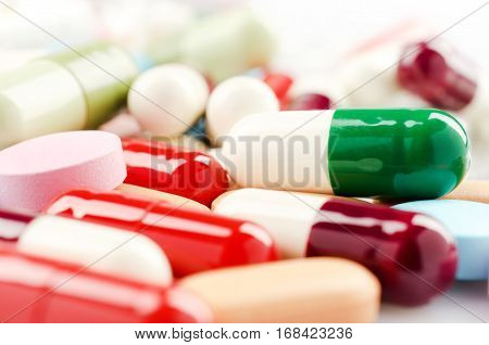 Medical theme. Multicolored Isolated Pills and Capsules on the White Surface. Closeup