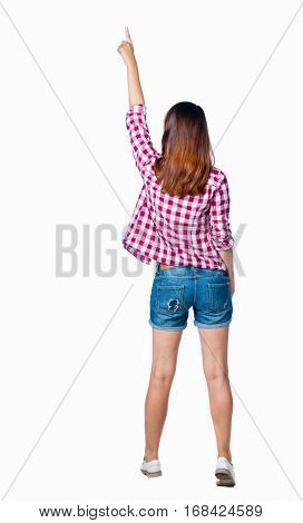 Back view of  pointing woman. beautiful girl. Rear view people collection.  backside view of person.  Isolated over white background. Girl in shorts and a plaid shirt is pointing to the top.