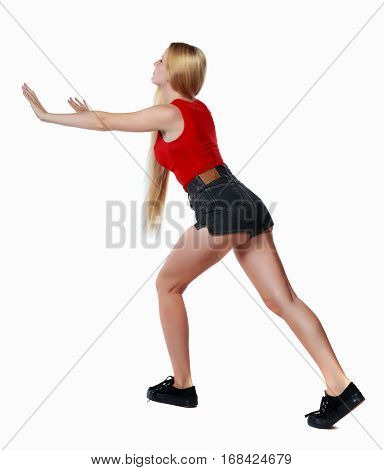 back view of woman pushes wall.  Isolated over white background. Rear view people collection. backside view of person. Long-haired blonde in shorts shove the wall in front of him.