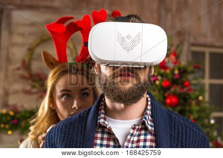 Happy couple using virtual reality headset at christmastime