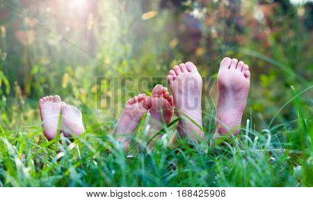 Happy children lying on green grass outdoors in spring park