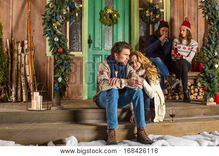 Young couple sitting embracing on stairs at christmastime