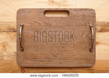 Wooden serving board with metal handles on restaurant table shot from above