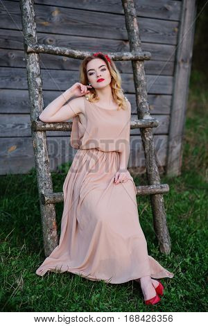 Yong Elegance Blonde Girl At Rose Dress On The Garden Background Wooden Staircase.
