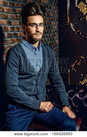Imposing handsome man in elegant formal clothes and glasses. Fashion hair styling, barbershop. Brick wall background. Business style.