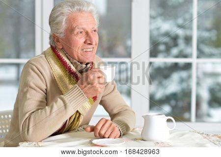 smiling senior man sitting near window in cafe