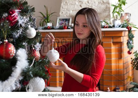 x-mas, winter holidays and people concept - happy young woman decorating christmas tree with ball at home