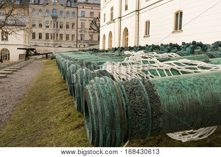 Many ancient metal artillery cannons along the white wall