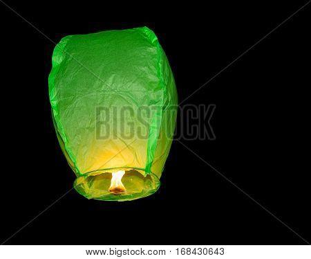 Green paper lantern floating into dark sky