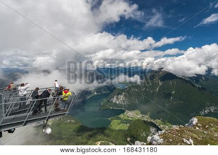 Tourists on a viewing platform. High above the ground. A delightful view of the valley, lake and mountains