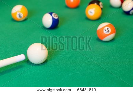 Pool balls with cue on green baize table