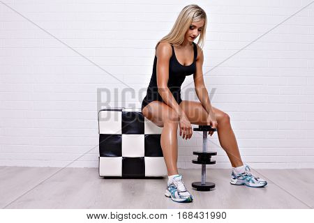 Side view of sexual blonde in bodysuit sitting on checkered poof and doing exercises with dumbbells