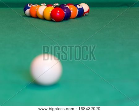 Pool balls with cue ball on green baize table
