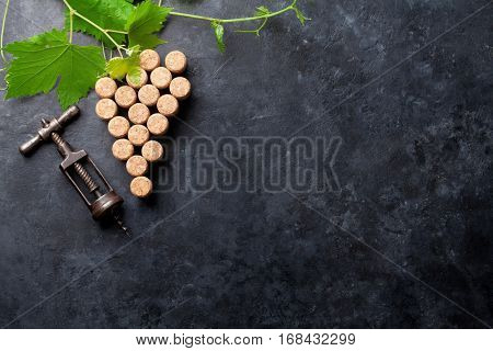 Wine corks grape shape, corkscrew and vine on stone table. Top view with copy space for your text