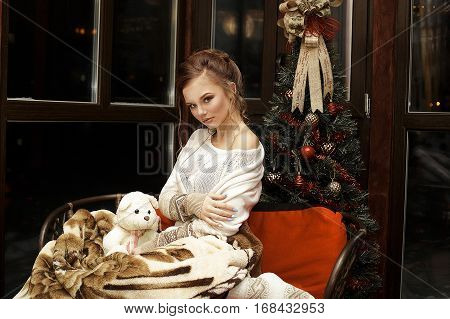 Cute attractive girl wearing in white clothes sitting on sofa with warm blanket near the window and hug self. Pretty girl sit on sofa in comfortable apartment with toys and cozy atmosphere.