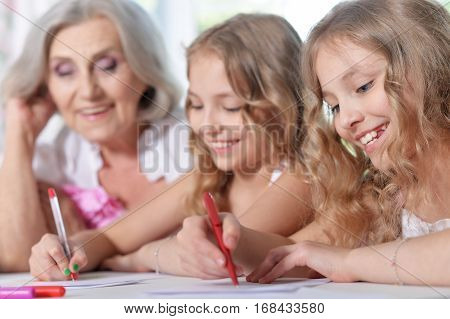 Portrait of a granny with her granddaughters doing homework