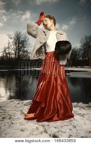 Nice woman in stylish dress posing in winter park