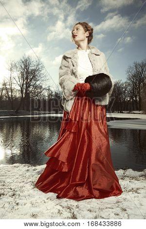 Beauty in red apparel posing in winter park