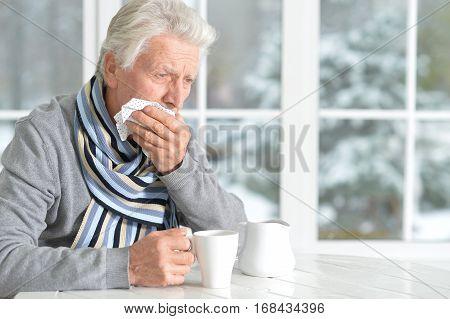 mature man having a toothache, holding handkerchief