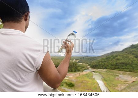 Man holding water bottle in his hand and nature view.