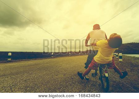 Father and son are  happy and funny with bike on the road and nature view.