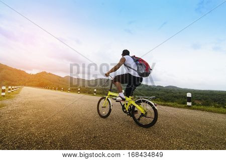 Man Asian backpack with his bike and sunshine view.Zoom in