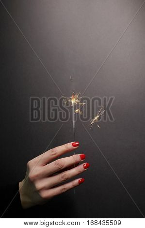 Sparkler in woman hand with red nail polish on grey background.