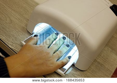 Closeup of the hands of a woman inside a UV lamp curing her recently applied gel nail polish at a salon