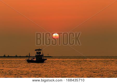 Orange Sky With Sunset Over Sea , Shore And Fishing Boat