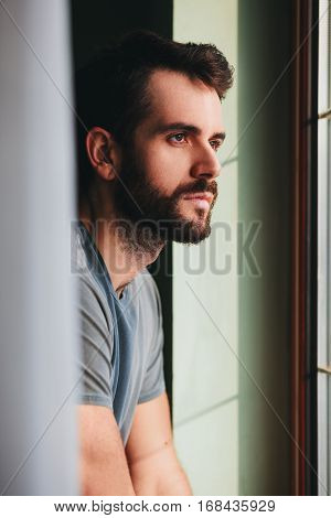 Young man standing by the window looking outside