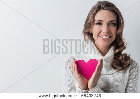 Happy young smiling woman with pink paper heart