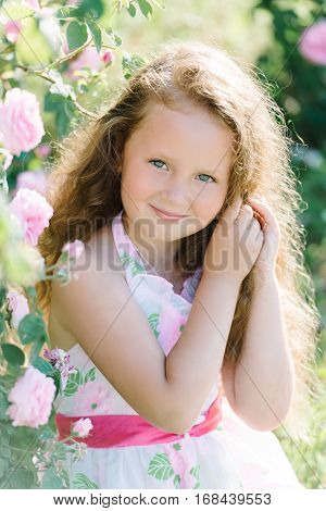 Close up portrait of a cute curly toddler girl outdoor in a rose garden smelling the flowers. Summer, Childhood.
