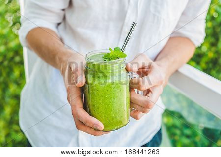Mason Jar Mugs Filled With Green Spinach, Banana And Coconut Milk Health Smoothie With With A Spoon