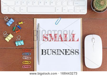 Text Small business on white paper which has keyboard mouse pen and office equipment on wood background / business concept.