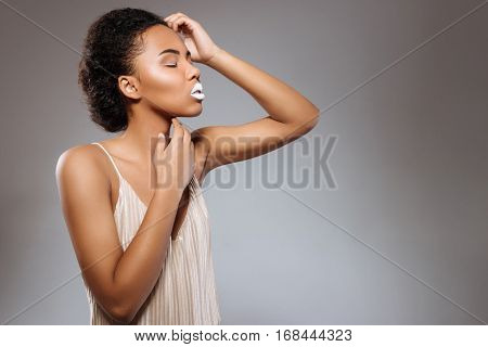 Striking a pose. Young fresh gorgeous model accentuating her interesting makeup while wearing a matching white dress and standing isolated on grey background