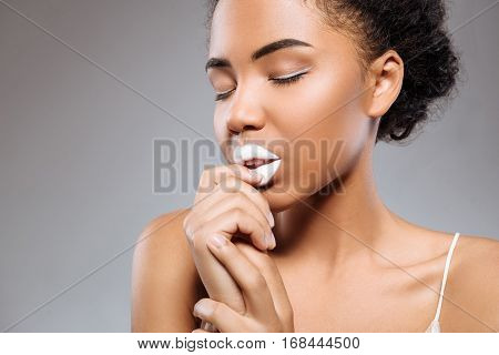 White can be creative. Magnificent slender young woman demonstrating an unusual make up accentuating her exotic beauty while working with a professional photographer in a studio