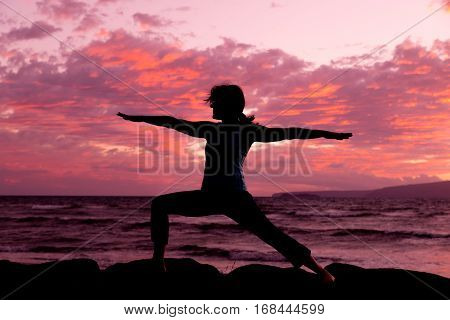 a woman silhouetted practicing yoga on a maui beach at sunset