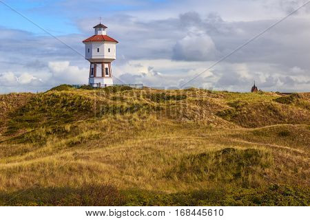 A lighthouse and water tower at the island of Langeoog East Frisian islands Lower Saxony Germany